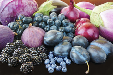 Blue and purple food. Berries, fruits and vegetables on a black background.