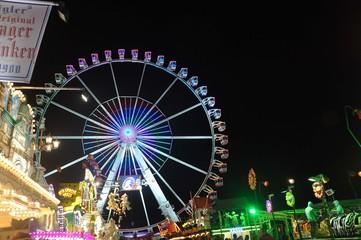 Ein beleuchtetes Riesenrad vor Nachthimmel,