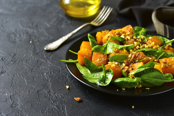 Roasted pumpkin salad with spinach and walnut on a black plate.