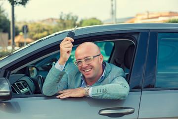 Fototapeta Handsome business man showing keys of his new car. Retro toned p obraz