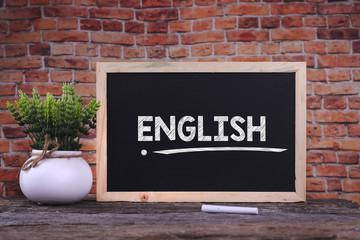 ENGLISH word on blackboard with green plant.