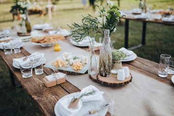The composition of flowers and greenery standing on served table in the area of wedding party