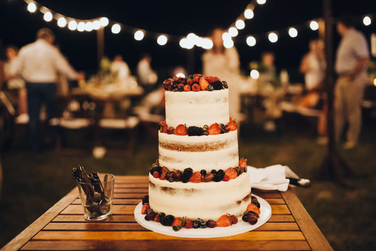 three-level white wedding cake decorated with cream and berries, stands on a table in the banquet area