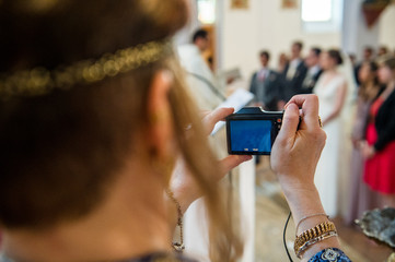 Woman with camera taking photographs of newlyweds at religious wedding churh ceremony