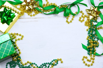 Christmas gifts, colorful ribbons and bows with green and gold beads form a border around a rustic, white washed wooden table top. Overhead perspective. Copy space