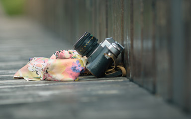 old camera and a handkerchief forgotten on wooden bench