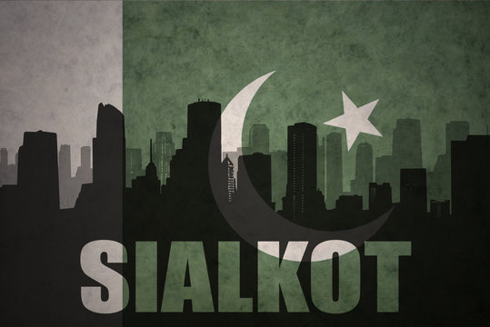 abstract silhouette of the city with text Sialkot at the vintage pakistan flag background