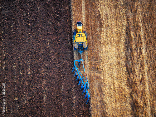 Wall mural Tractor cultivating field at autumn, aerial view
