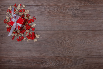 Christmas decorations on wooden background with copy space for text. Red-white small ornaments around red gift box. Top view.