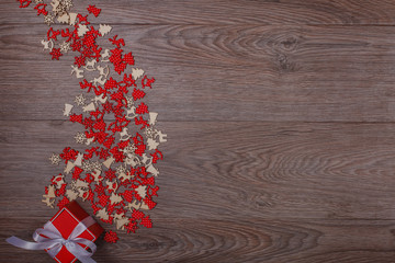 Christmas decorations on wooden background with copy space for text. Red-white chaotic small ornaments and red gift box like a falling star on the left. Top view.