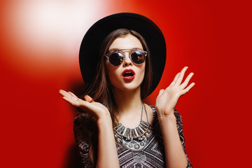 Indoor portrait of a young beautiful woman acting thrilled. Model expressing joy and excitement with hands and face. Girl wearing sunglasses, looking at camera. Close up. Red wall as background