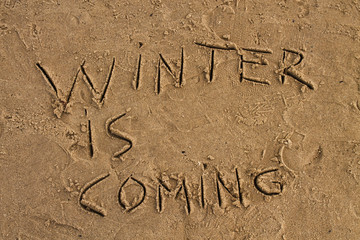 Winter is coming  sign on the wet sand beach