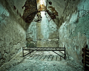 Cot in empty crumbling prison cell at Eastern State Penitentiary