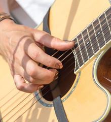 girl's hand playing guitar