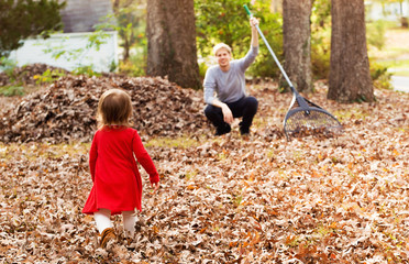 Toddler girl running to her father raking leaves in the fall