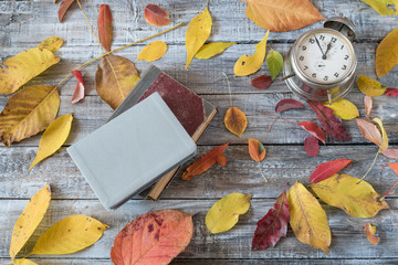 Vntage books and clock on wooden table. Autumn composition.