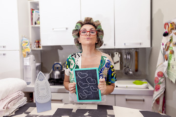 mature housewife woman with curlers shows a board with hearts