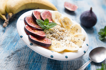 healthy breakfast: oatmeal with fresh figs, bananas,  coconut mi