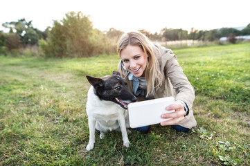 Beautiful woman with dog in taking selfie, nature.