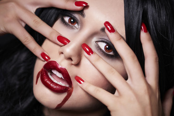 Beautiful vampire face with her fingers