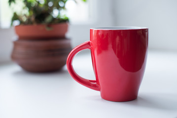 Red mug with tea or coffee on white table by the window