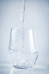 Filling a glass with water on white background