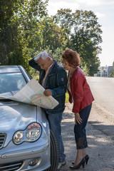 Rentnerpaar hat sich verfahren und schaut auf Straßenkarte