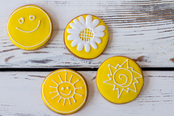 Top view of iced cookies. Round biscuits on wooden background. Flower and smiling sun. Art starts from imagination.