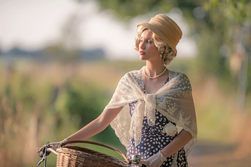 Retro woman dressed in 1930s fashion standing with bicycle in ru