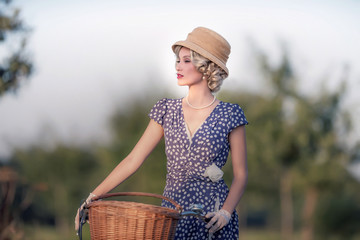 Vintage 1930s fashion woman in blue summer dress standing with b