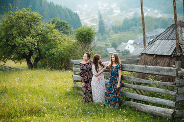 Girls girlfriend dresses rest on the nature in a beautiful mountain meadow
