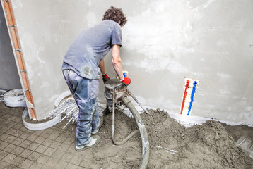 Employee performs sand and cement screed floor.