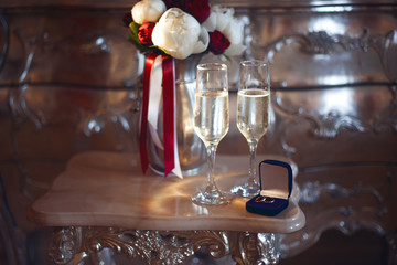 Bridal bouquet and wedding rings in the box with two glasses of champagne