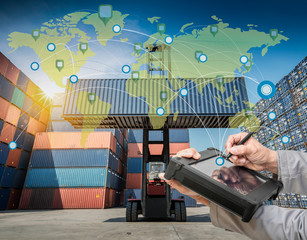 Wall Mural - Hand presses on world map with digital tablet,Industrial Container Cargo freight ship at dusk for Logistic Import Export background (Elements of this image furnished by NASA)