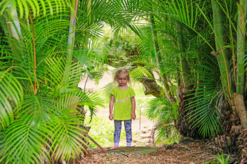 Little blond girl staying among palm trees outdoors