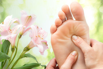 Macro detail of foot massage next to flowers.
