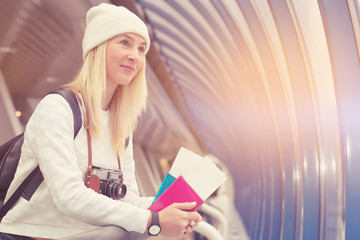 Young hipster girl is waiting her departure in airport terminal. Happy tourist girl with retro camera and leather black bag, white modern hoody and 