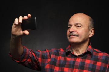 Elderly man doing selfie on a smartphone.