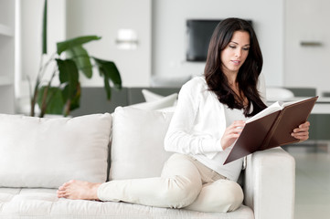 Young Woman Lounging in Living Room Reading Book