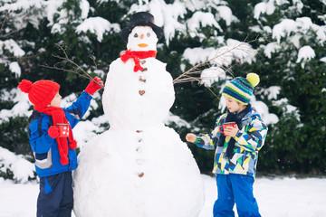 Happy beautiful children, brothers, building snowman in garden a