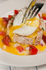 Tuna with poached egg and cherry tomatoes in a white bowl and a silver fork piercing the yoke and enveloping the tomatoes