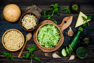 Raw ingredients for vegetarian dinner recipe. Preparing veggies cutlets or patties for burgers. Zucchini quinoa veggie burger with pesto sauce and sprouts. Top view, overhead, flat lay