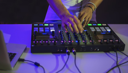 Hands of a DJ using a mixer