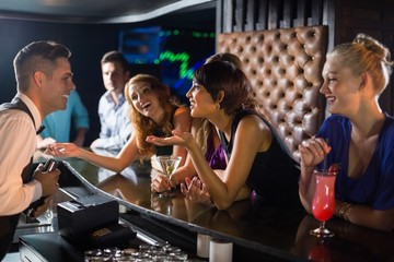 Beautiful woman interacting with waiter at bar counter