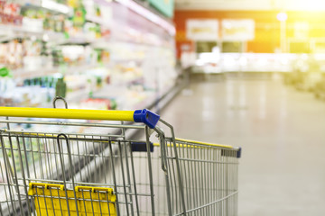 Cart at the grocery store. Abstract blurred photo of store with trolley in department store bokeh background. New ideas in trade and business.Advertising of food products. Shopping at the hypermarket.