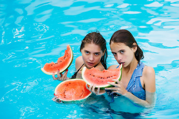 women with watermelon in swimming pool