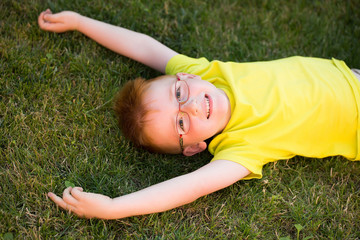 Happy baby boy with red hair in glasses on grass
