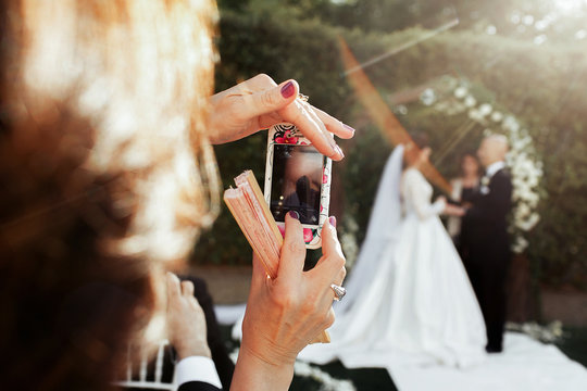 Lady takes picture of wedding couple on her iPhone