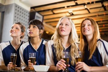Female fan watching football at bar counter