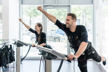 Two sportive people having training session in EMS studio gym